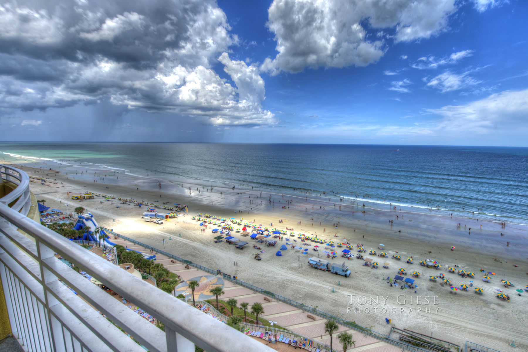 Wyndham Ocean Walk Resort condo balcony ocean view as rain starting to fall from clouds on a blue sky day overlooking Daytona Beach, Florida. Photography by Tony Giese