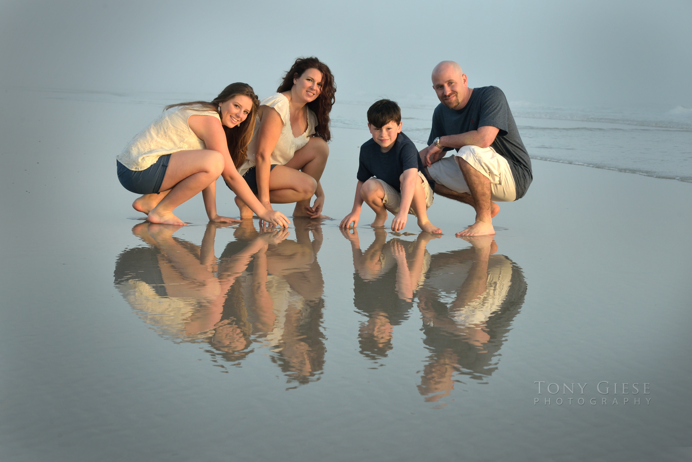 Reflection falls on the water as the tide pulls out for wonderful family portrait by Tony Giese Photography.