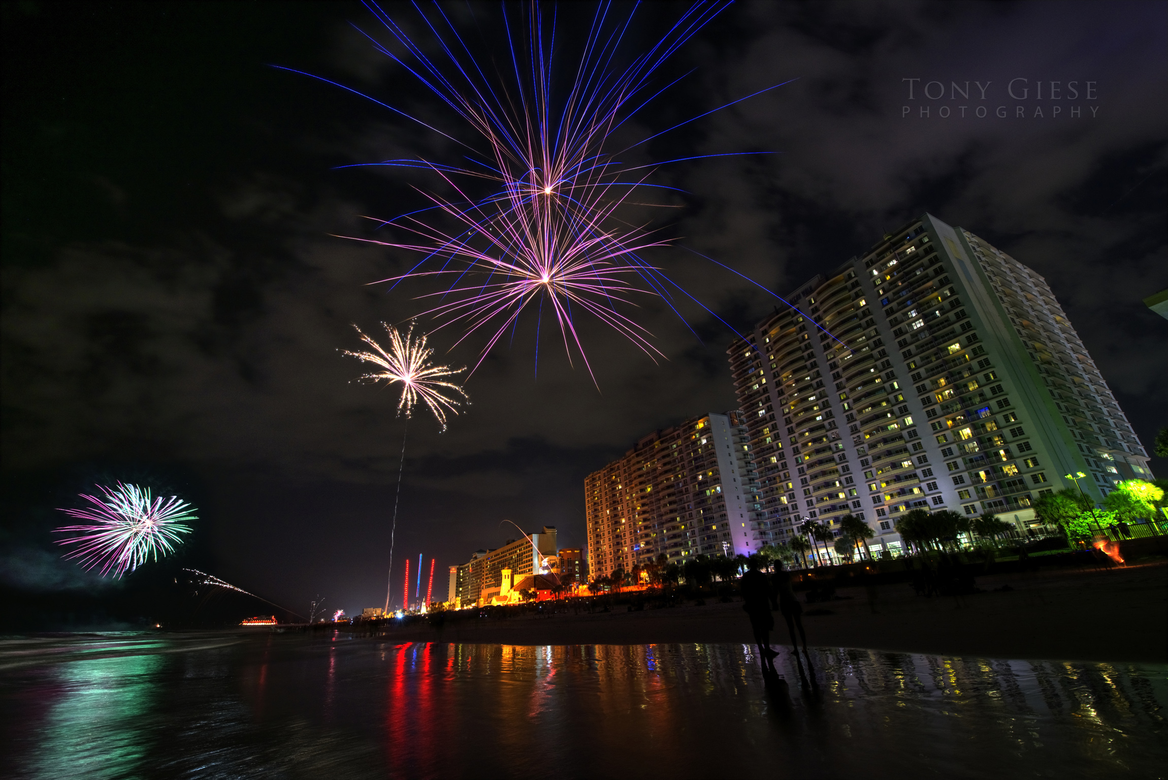 Perspective view of fireworks going off up and down Daytona Beach.
