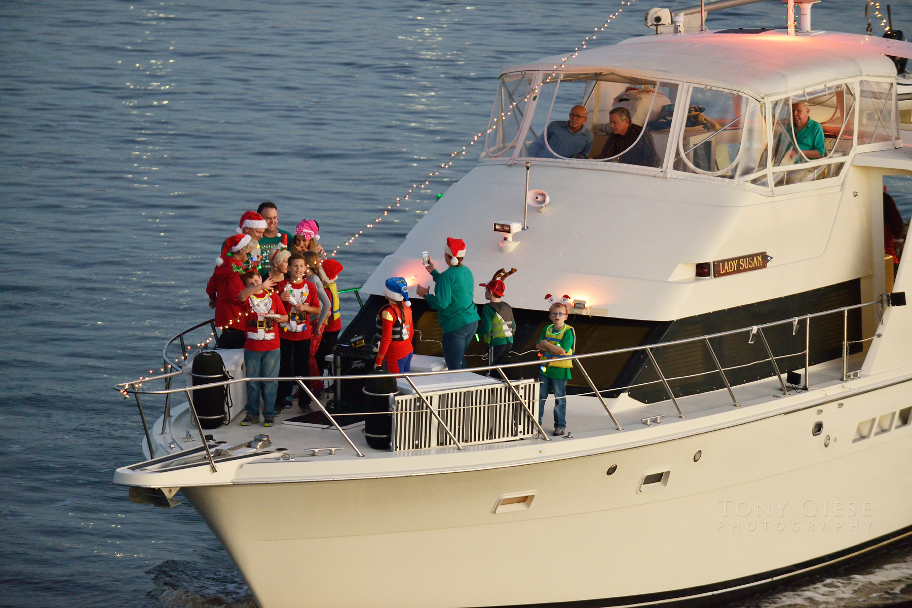 Costumed passengers gather for photograph on front of cruising yacht.
