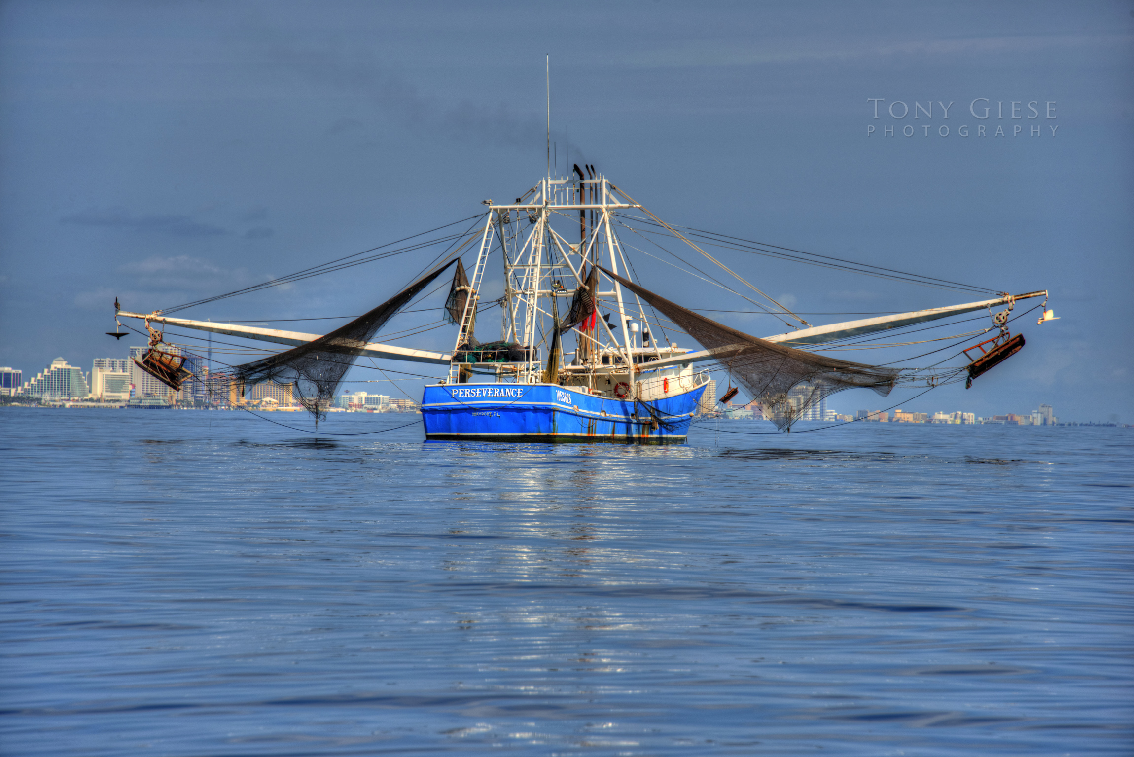Shrimp boat on blue water with nets up offshore of Daytona Beach blue water skyline.