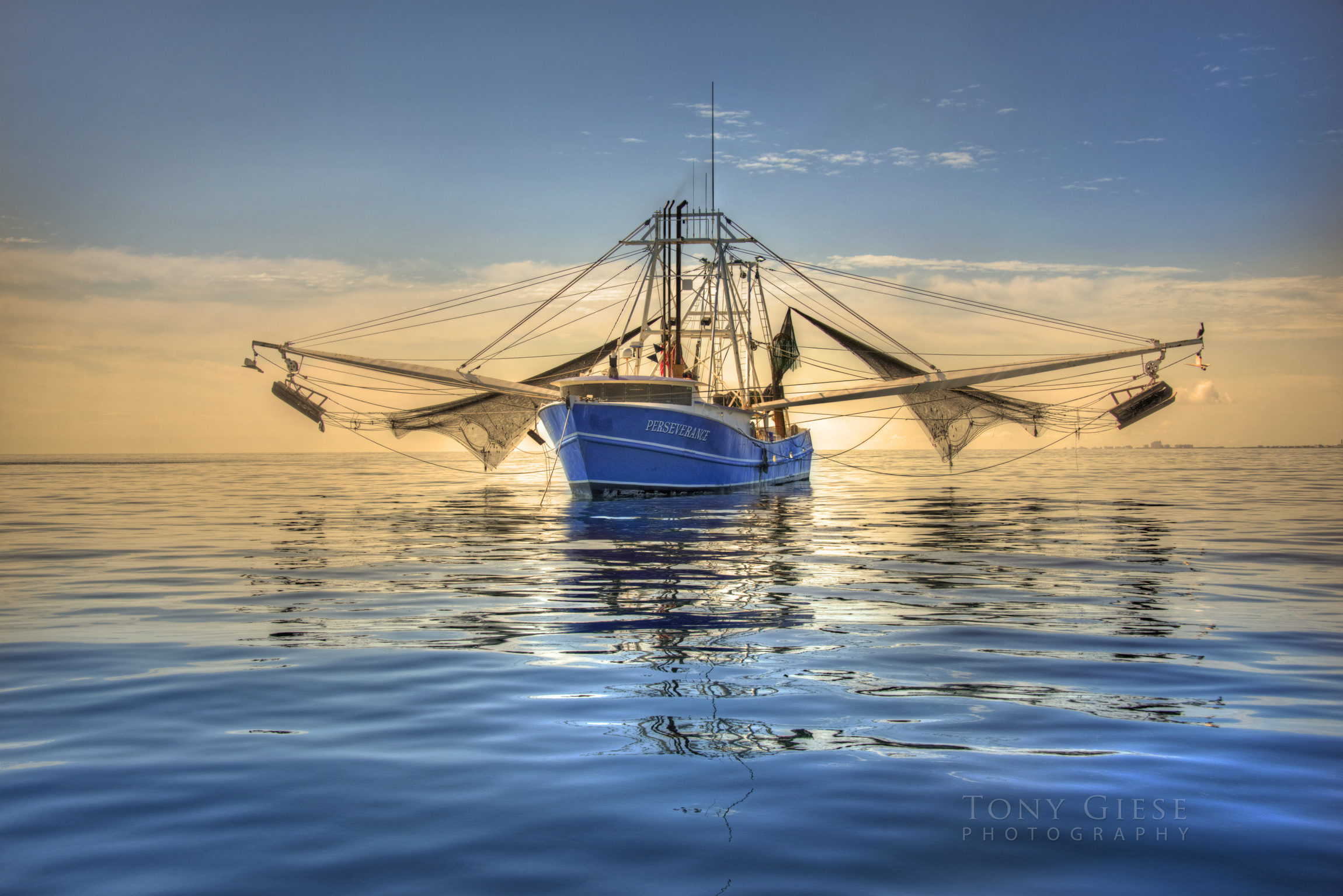 Shrimp boat resting with nets up. Upon calm ocean. Offshore Daytona Beach.