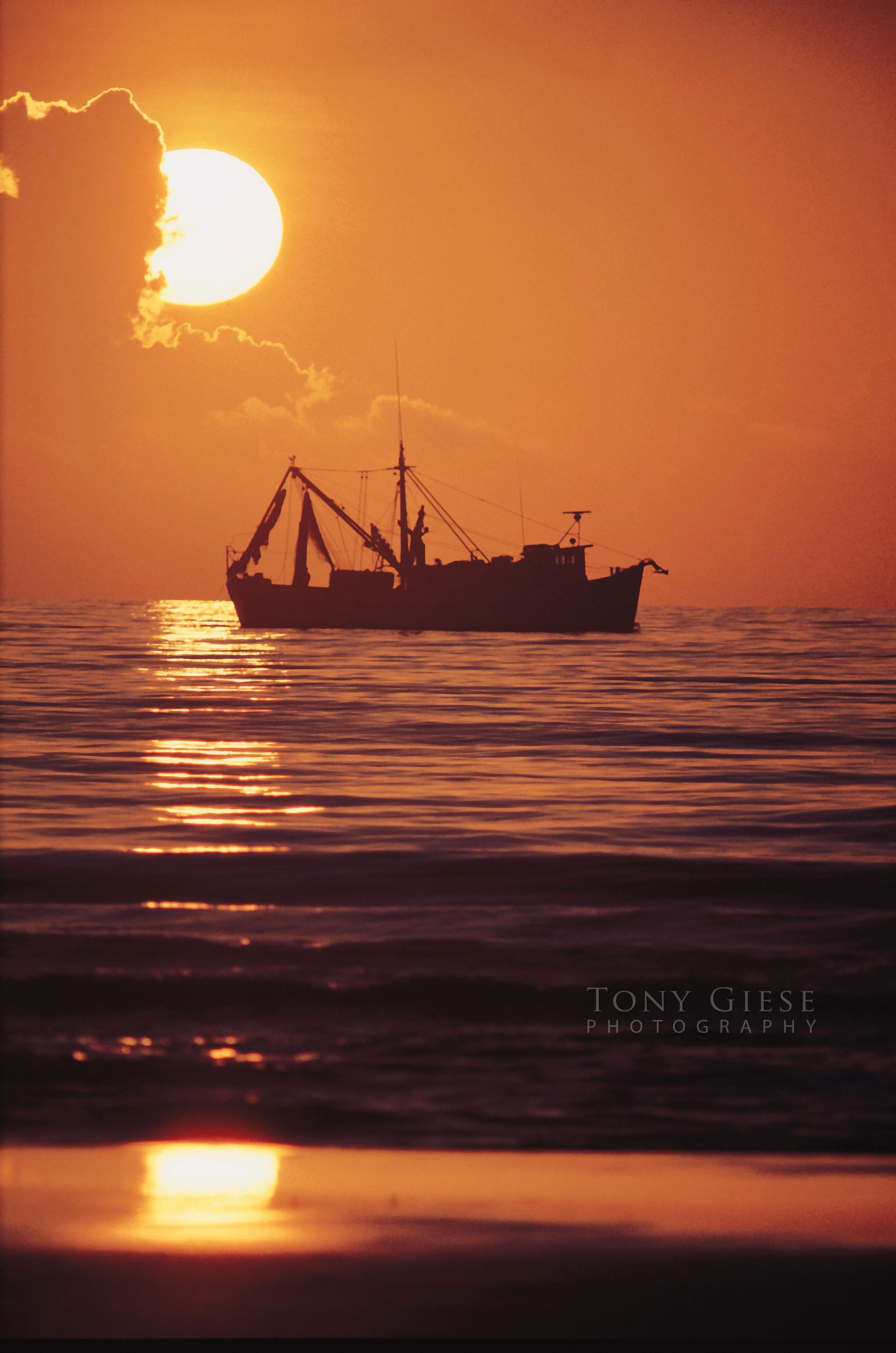 Early morning sunrising over shrimp boat offshore Daytona Beach, Florida.